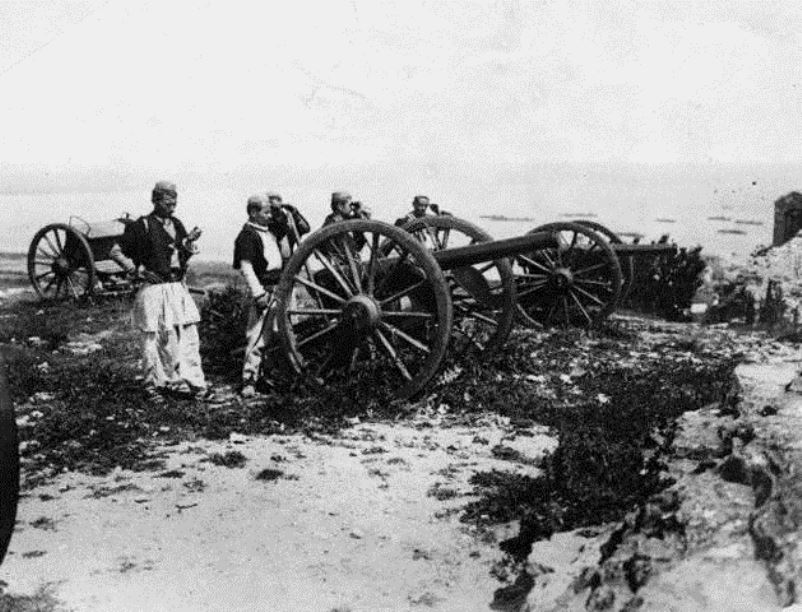 Albanian artillery crews man obsolete guns in traditional dress, ca. 1914