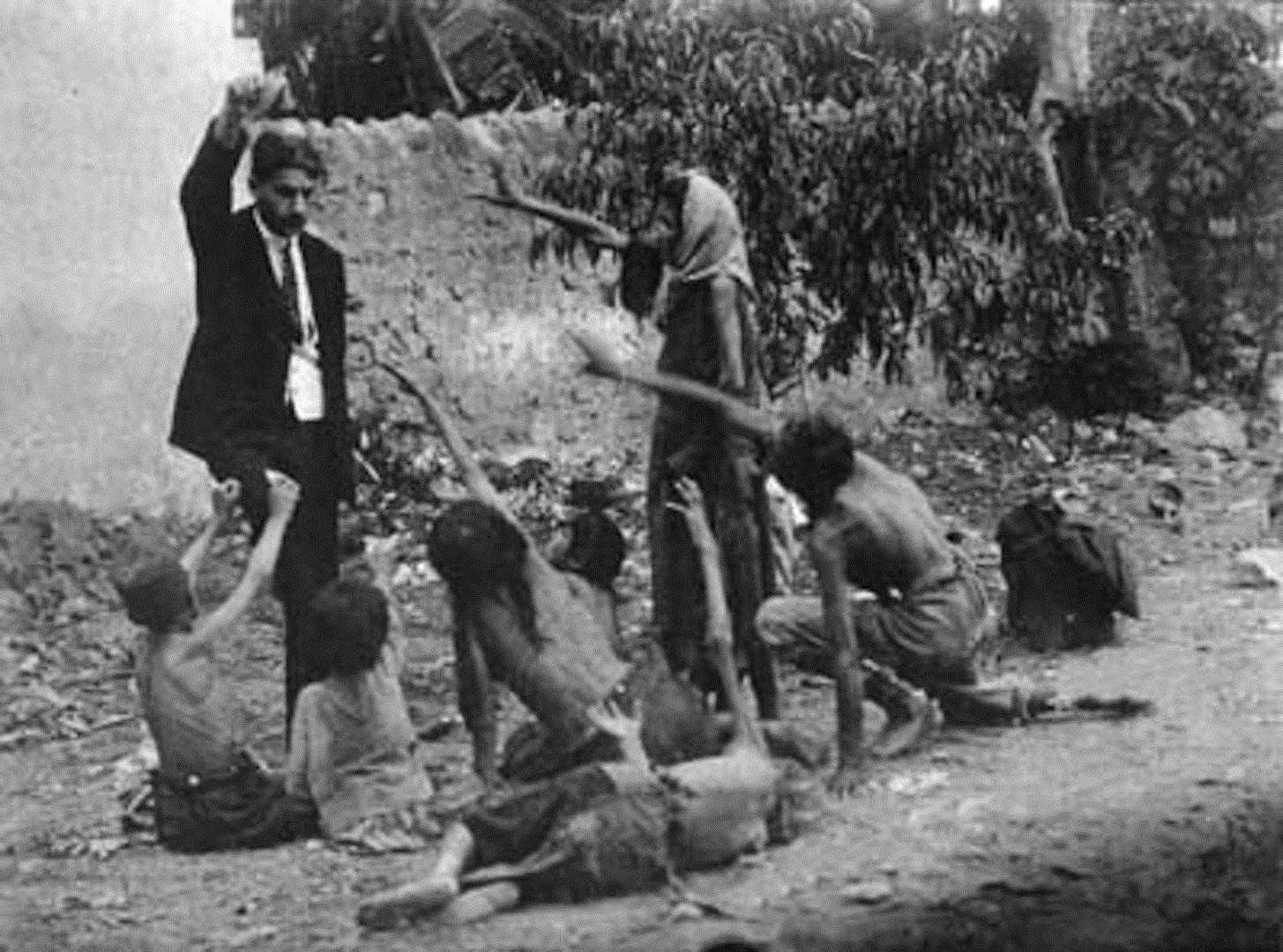 A Turkish official teases starving Armenian orphans with a loaf of bread