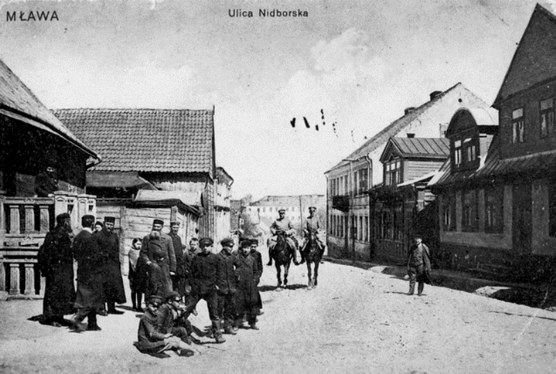 A prewar photo of Mlawa Jews in traditional dress as Russian cavalry patrol the streets