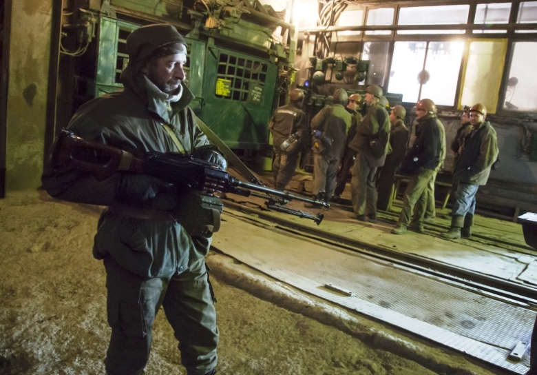 Conflict mineral: a Russian separatist watches coal miners in Donetsk, Ukraine